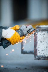 Worker cutting metal with grinder at construction site.Sparks while grinding iron