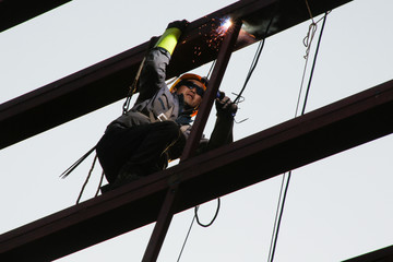 A worker welds as he stands on the metal frame of a building at a construction site in Beijing