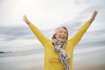 Carefree energetic senior woman playing around on beach in fall