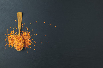 Red lentils in wood spoon on a black stone table background.