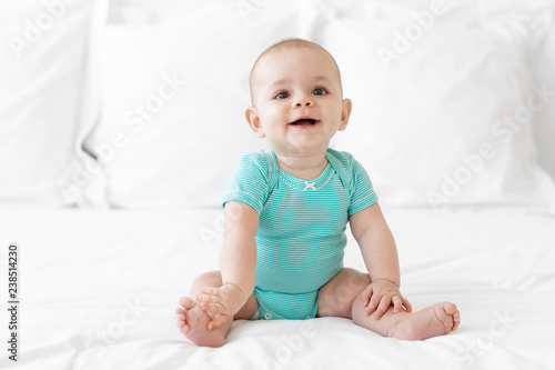 d55149e67696 Happy baby in teal onesie sitting on white bed