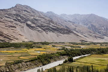 Fertile Wakhan Valley with Panj river near Vrang in Tajikistan. The mountains in the background are the Hindu Kush in Afghanistan