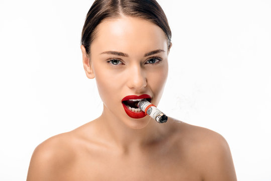 beautiful naked girl smoking rolled dollar banknotes and looking at camera isolated on white