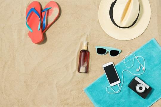 vacation and summer holidays concept - smartphone with earphones and film camera on towel, straw hat, sunglasses, flip flops and bottle of sunscreen oil on beach sand