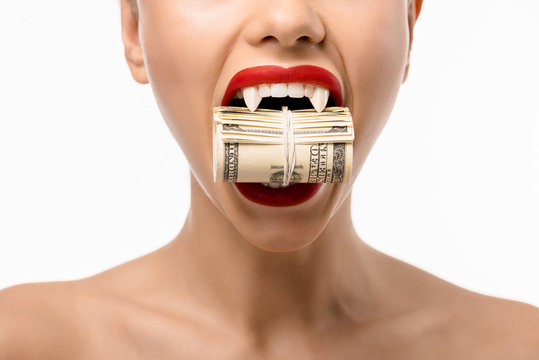 cropped shot of naked girl with vampire teeth holding rolled dollars in mouth isolated on white