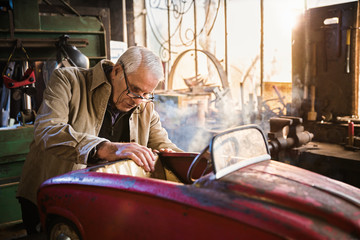 Senior man in his workshop repairing an old fashioned pedal car