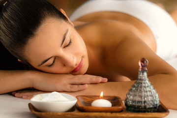 Attractive woman relaxing in spa next to candle and essential oil.