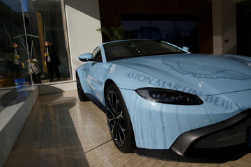 Shadow of the Aston Martin brand logo is cast onto the bonnet of a luxury sports car at a dealership in Beijing