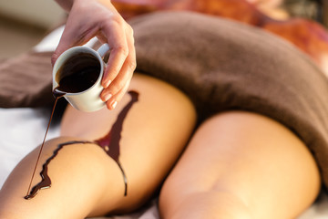 Hand pouring hot chocolate massage oil on female leg.