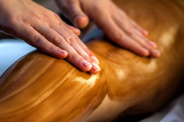 Hands massaging female calf muscle with hot chocolate oil.