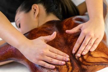 Hands massaging hot chocolate on female back.