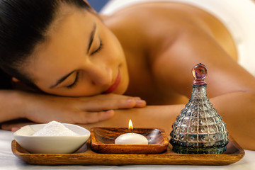 Massage oil and candle with out of focus girl in background.