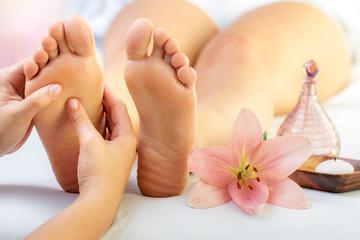 Reflexologist massaging female feet.