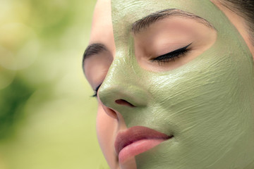 Woman having cosmetic facial seaweed treatment in spa.