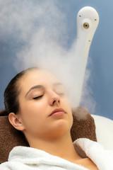 Woman having facial steam treatment in spa.