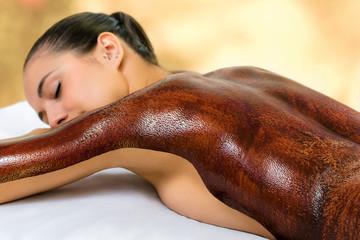 Young woman enjoying hot chocolate massage in spa.