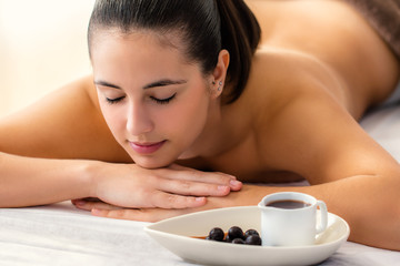 Young woman in spa with chocolate wax massage products.
