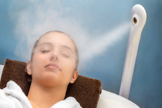 Young woman having thermal steam treatment on face.