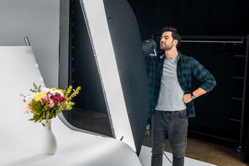 handsome young photographer working with lighting equipment and photographing beautiful flowers in studio