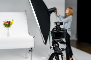 close-up view of photo camera and young woman working with lighting equipment in studio