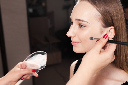 makeup artist dabbing the mixed foundation on a face skin of a young beautiful happy client. concept of professional make up training