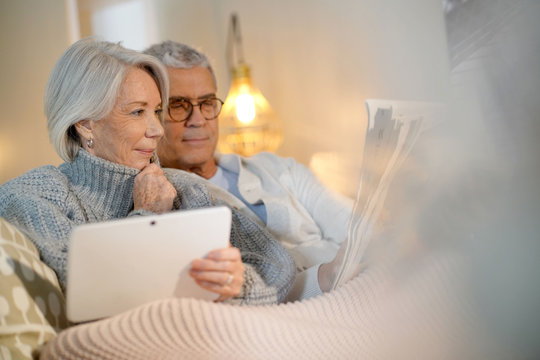 Senior couple relaxing at home on couch with tablet and newspaper