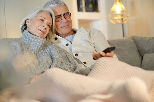 Attractive senior couple on couch at home watching TV