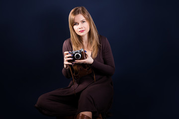 Portrait of beautiful woman holding retro photo camera on a dark blue background