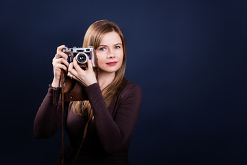 Portrait of beautiful woman holding retro photo camera on a dark blue background