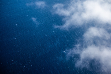Wall Mural - Aerial view of the sea surface with some clouds above it
