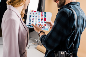 cropped shot of photographer and model looking at photos in studio