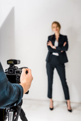 cropped shot of photographer with camera shooting beautiful young woman in studio
