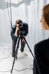cropped shot of young photographer shooting beautiful female model in studio