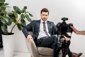 cropped shot of photographer taking pictures of handsome man in stylish suit in studio