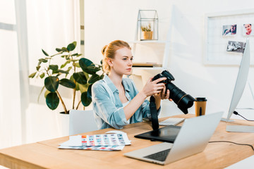 beautiful young photographer holding camera and retouching photos in office