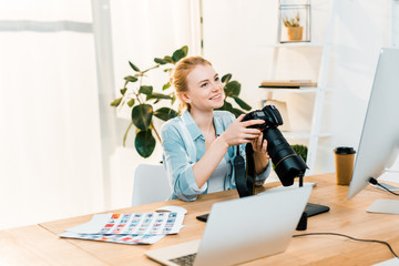 beautiful smiling young female photographer holding camera while working in office