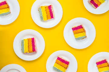 Bright cake pattern. Top view set of rainbow cake slices on white round plates on yellow background. Happy bithday, party layout concept. Selective focus. Copy space.
