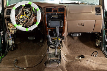 Car steering repair, disassembled gearbox, old gearshift lever, steering wheel covered with protective film, cover removed and electric wires visible.