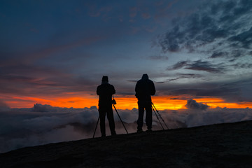 Two unidentified photographers take a photo of cloudy mountain landscape during sunrise.