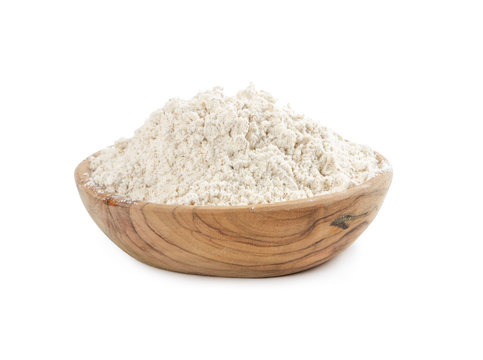 Whole wheat flour in wooden bowl isolated on white