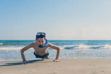 Happy and smiling boy in the snorkeling mask and tube on the sand on the beach. Travel and summer concept