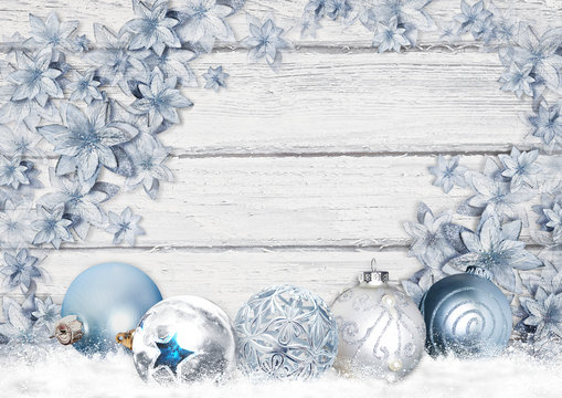 Christmas greeting card with beautiful balls and blue flowers on a wooden board