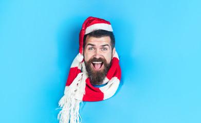 Christmas sales. Smiling guy in Santa hat breaks through paper wall. Happy man in Santa hat looking through hole in paper. Christmas, New Year, holidays, winter concept. Stylish guy in santa hat&scarf