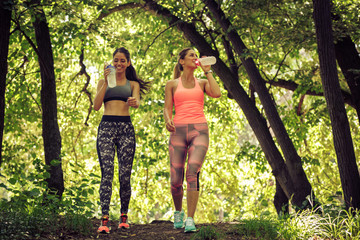 Two young female friends walking at the park.Relaxing after jogging.