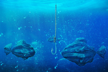 Сoncept of global pollution. In the open ocean floating trash bags in the form of fish. Save the planet.