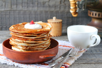 A stack of pancakes in a clay bowl near the old samovar on the gray wooden background.