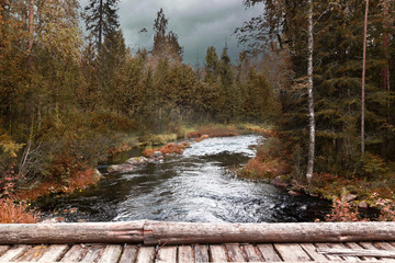 Storm clouds over the river and the autumn  forest wooden bridge