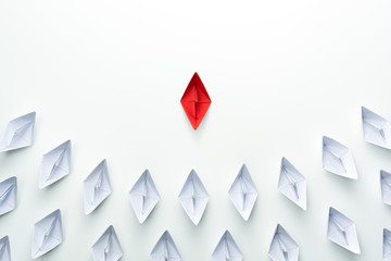 Leadership concept with red paper ship leading among group of white ships on white background.