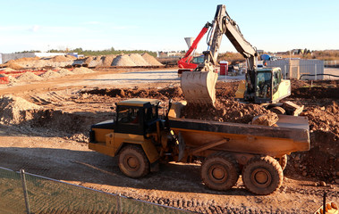 An excavator spills dirt and stone in the trailer of an heavy dumper truck at a newly opened construction site.