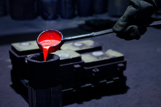 Hand mit Schöpfkelle gießt flüssiges Metall in Guss Form